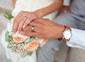 Close up photo of older couple embraced hands with engagement rings
