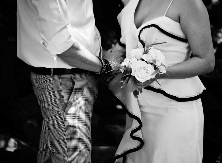 Monochrome photo of man and woman holding hands, faces hidden