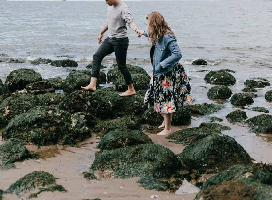 Man and woman hand-in-hand scrambling over rocks on seashore