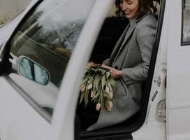 Woman smiling at receiving bunch of beautiful flowers while sat in car.