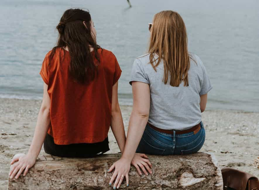 Two women in conversation sitting on a log on beach looking out to sea