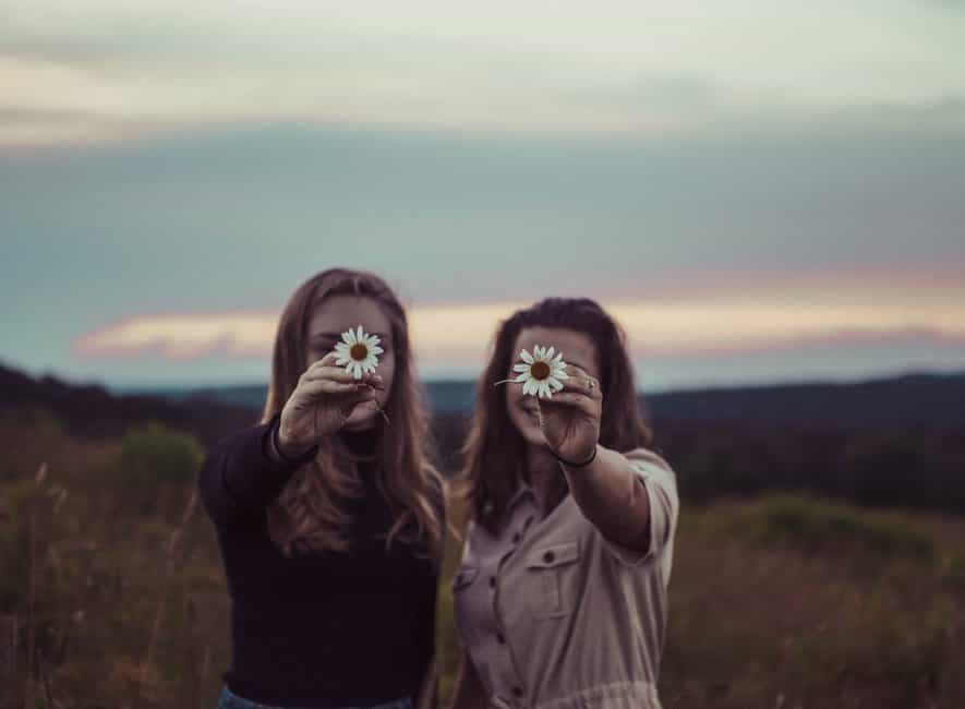 Photo of two women each holding a flower in front obscuring faces