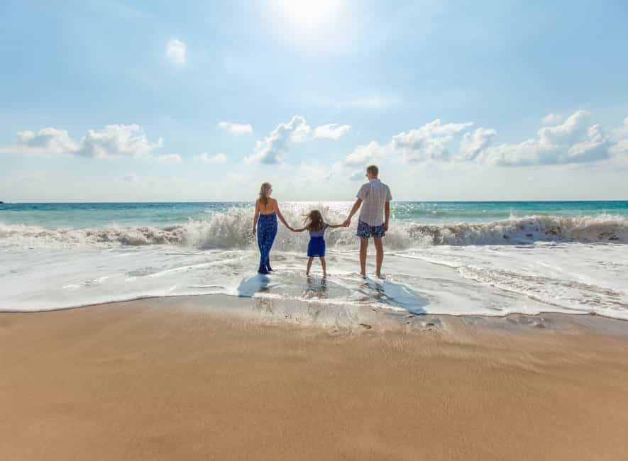 Man and woman holding hands with child between them on beach all facing the ocean surf on sunny day