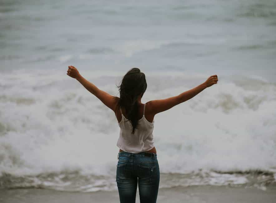 Photo of woman facing away with hands outstretched looking at the ocean surf