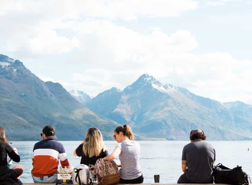 Back view of summer vacationers relaxing looking across water to mountains