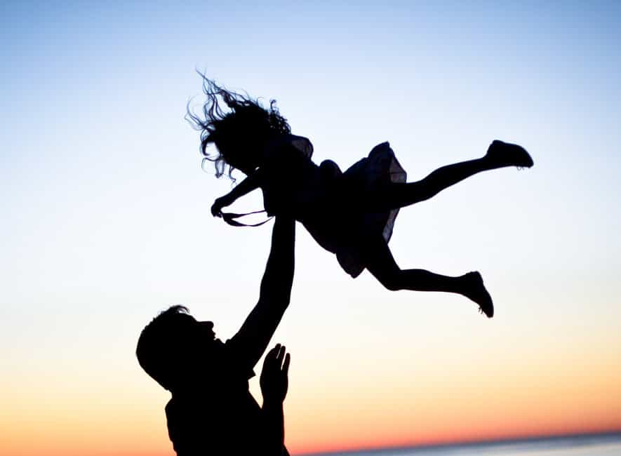 Silhouette sunset photo of dad entertaining young daughter