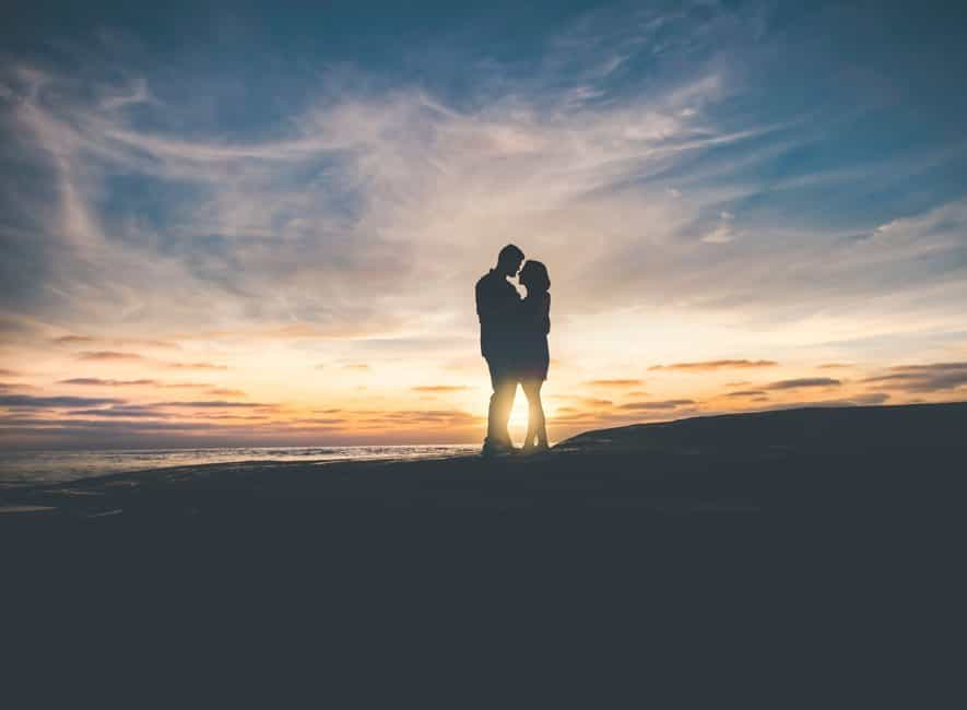 Silhouette photo of standing couple on beach at sunset about to kiss