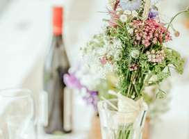 Photo of vase of flowers with blurred bottle of wine and glass in background