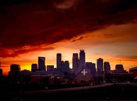 Photo of forbidding stormy sky above city skyline, red sunset