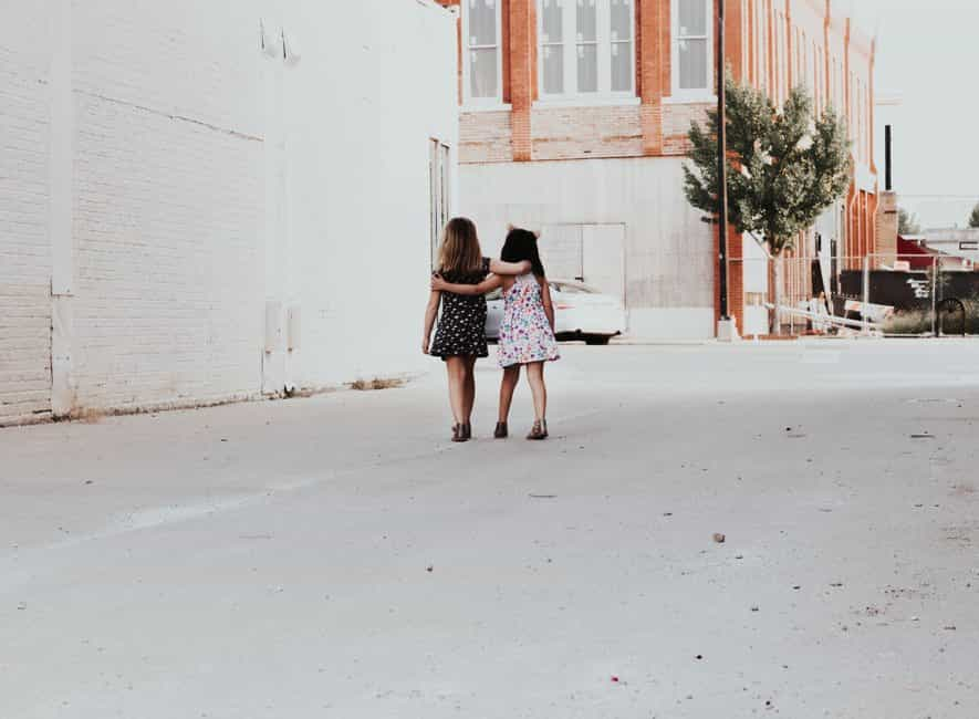 Back of head photo of two girls friends walking, arms around each other