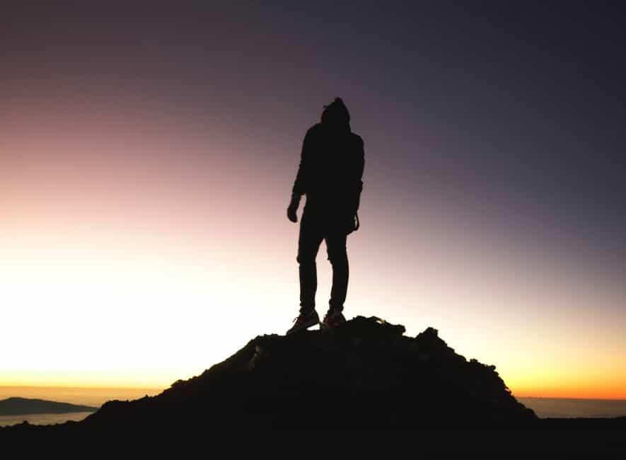 Night time photo of man standing on rock peak with sunset backdrop