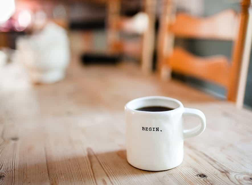 Cup of black coffee in white mug with the word Begin on the side