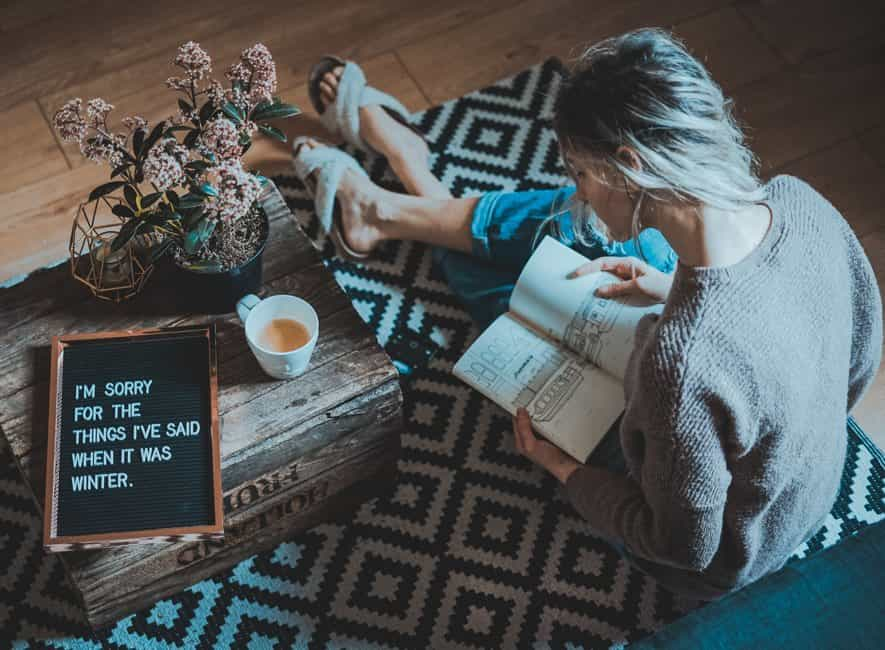 Woman sitting on mat reading with sorry message written on chalkboard