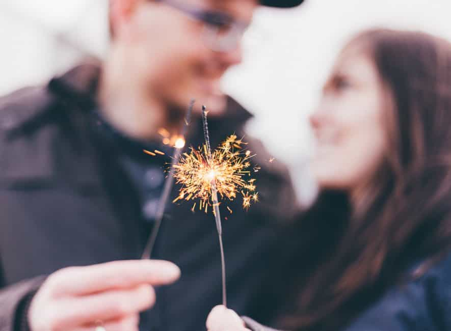 Man and woman with lit sparkler fireworks and laughing