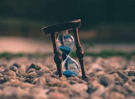 Elegant classic hourglass timer with blue sand passing through situated on pebble beach