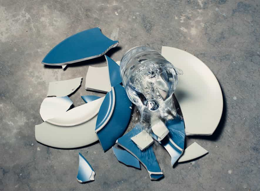 Smashed and broken plate and glass tumbler on floor
