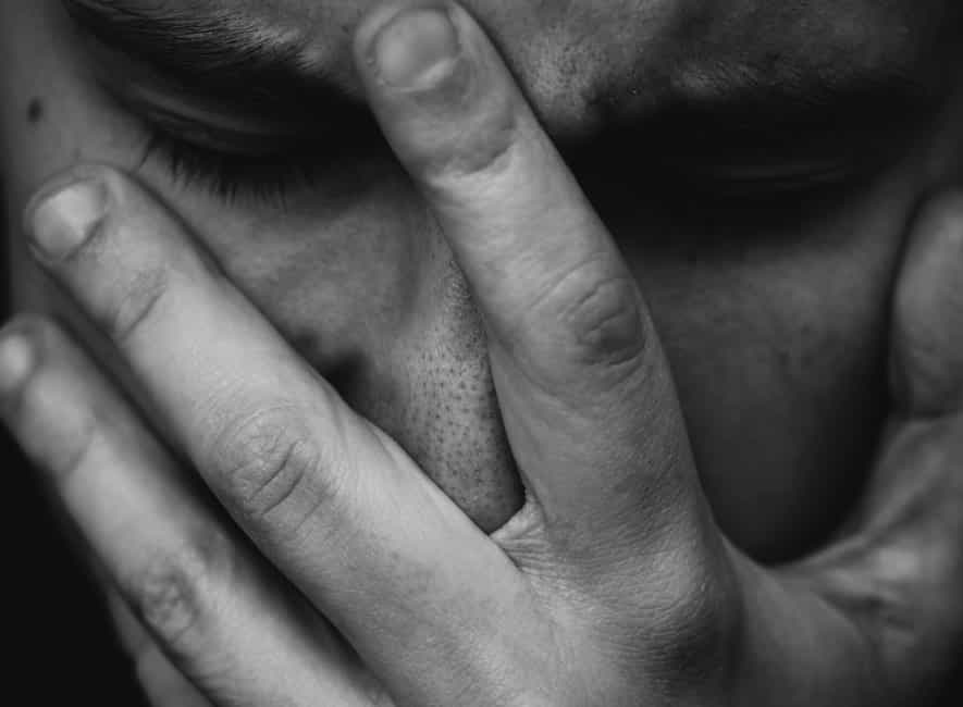 Greyscale photo of caucasian man covering face with hand