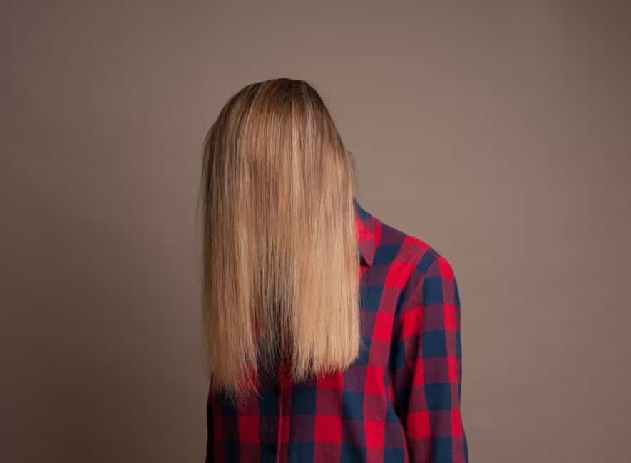 Young girl in tartan check shirt with beautiful long blond hair completely obscuring face