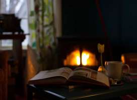 Open storybook in front of log burner fire