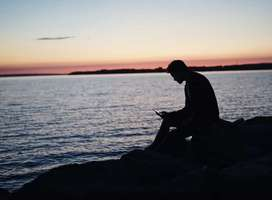 Man sitting on seashore rocks at sunset looking at smartphone