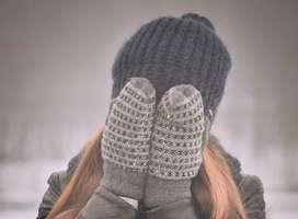 Young woman wearing winter gloves covering face with hands