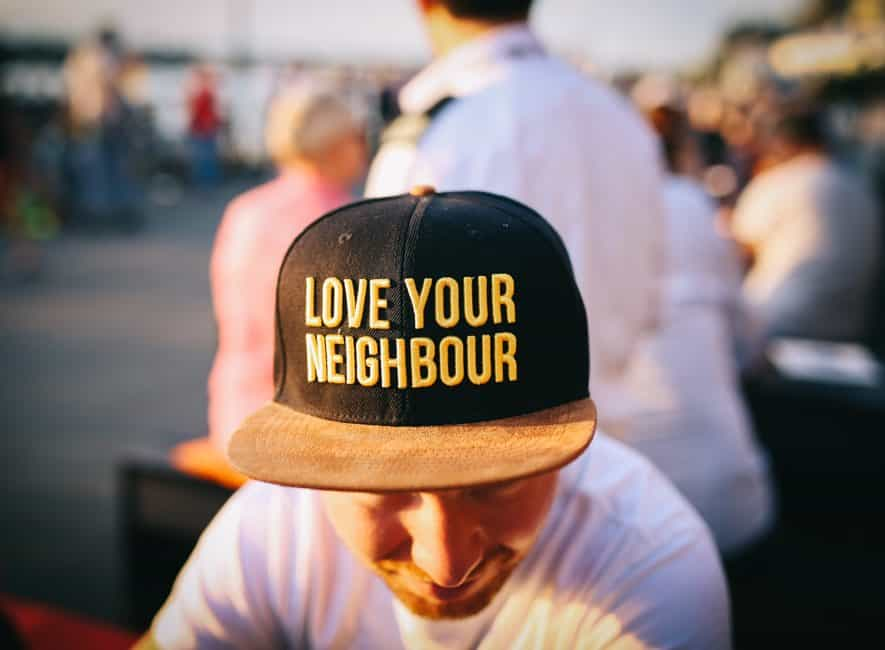 US man wearing love your neighbour baseball hat