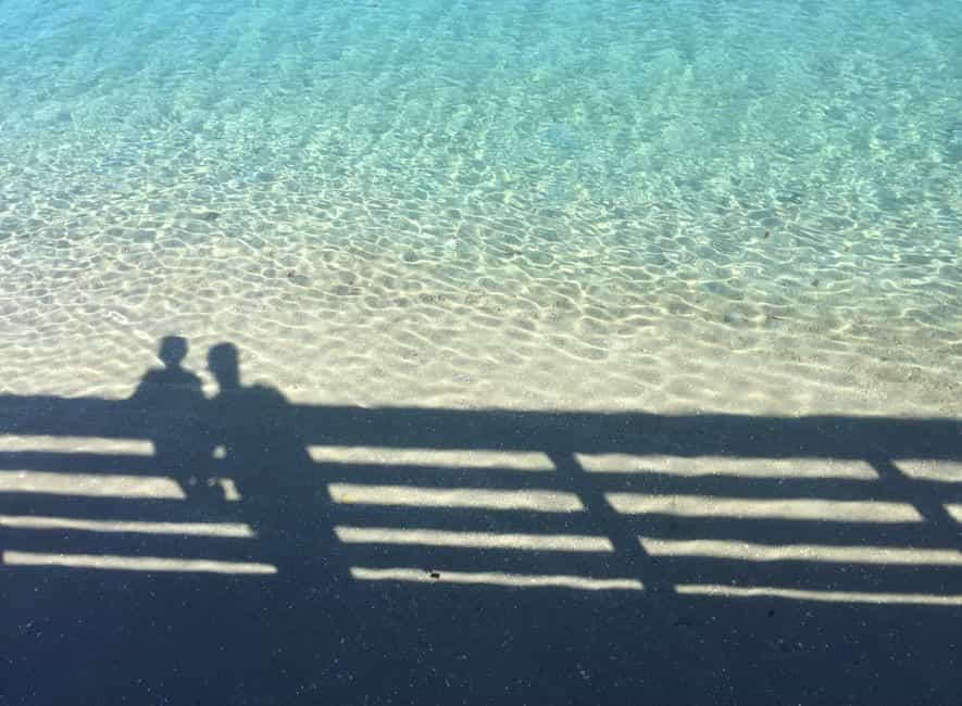 Shadow reflection in calm sea water of adult and child leaning over safety railing