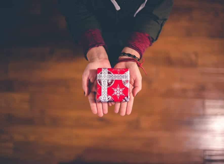 Person holding out small gift box wrapped in red and white