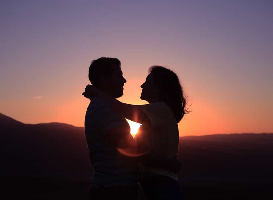 Silhouette of hugging couple at sunset, red sky