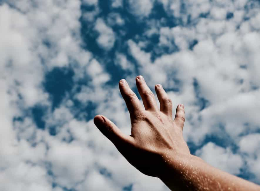 Hand reaching into cloudy sky
