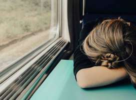 Woman sleeping on train slumped forward on to table.