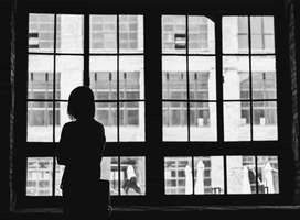 Black and white deep shadow image, woman staring out of window