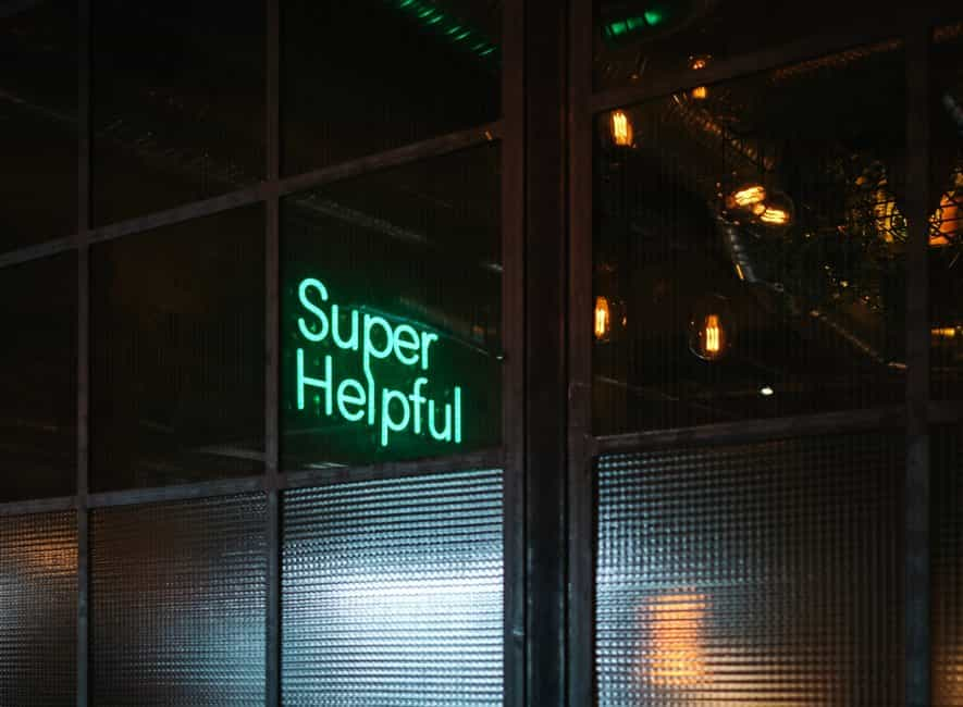Illuminated neon sign in business premises saying super helpful