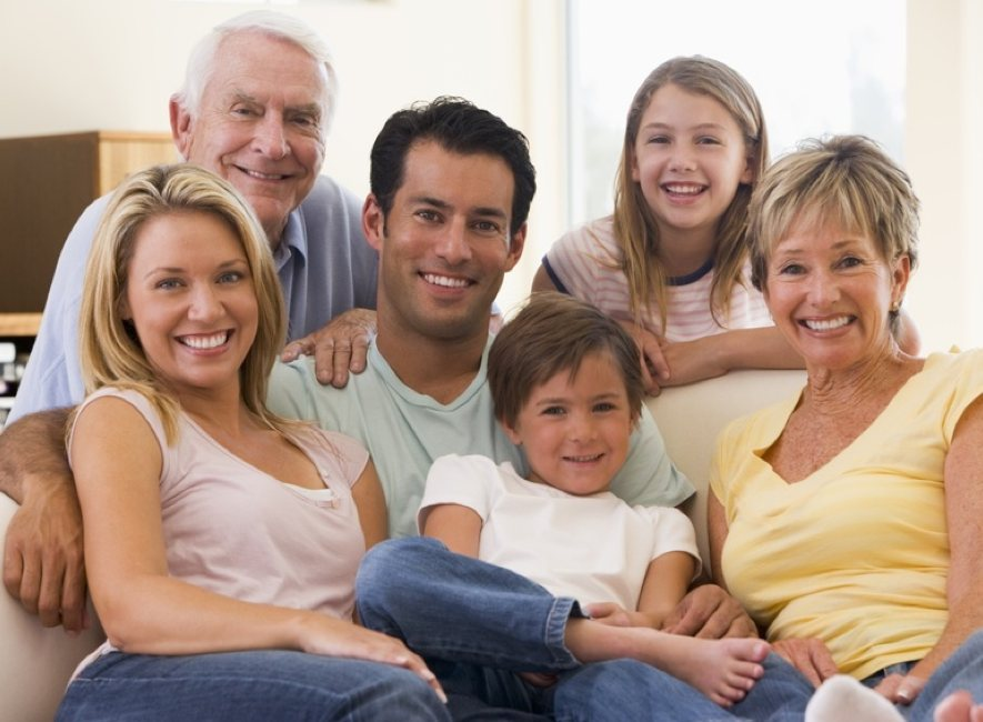 Photo of 6 members of smiling family siting, 3 generations.