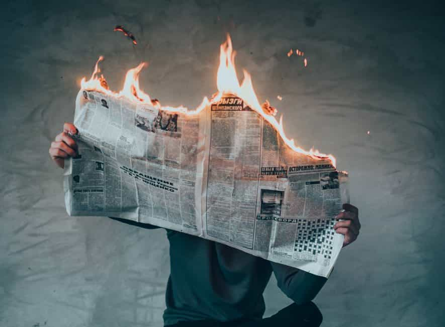 Man sat reading newspaper that is on fire
