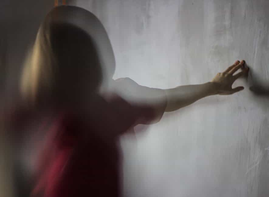 Abstract time lapse photo of woman facing and touching a grey wall