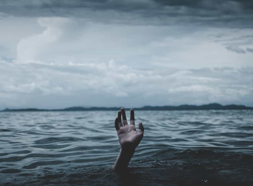 Hand reaching out above surface of seawater
