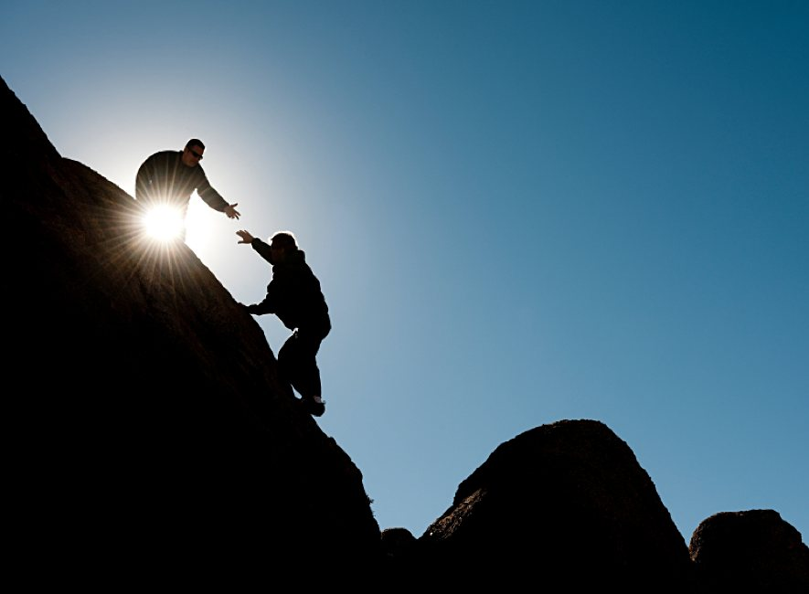 Two people on mountain, one with hand outstretched to other.