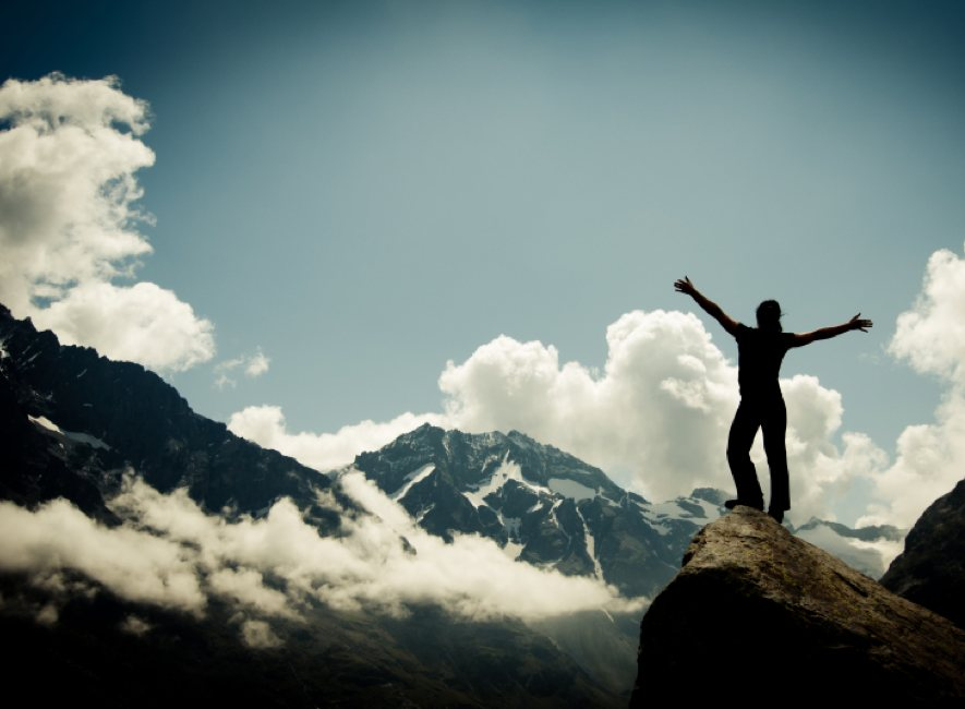 Person standing on mountain top arms outstretched in triumph.