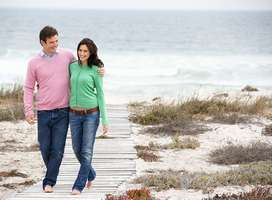 Married couple arm in arm walking on beach