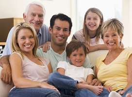 Photo of family sitting, three generations, smiling.