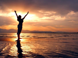 woman-on-sunset-beach-arms-outstretched-272x203