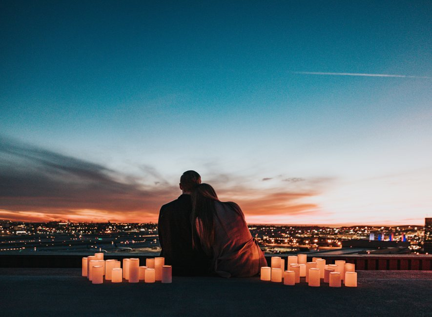 Couple looking at evening sky over city.