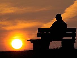 Man on bench watching sunset