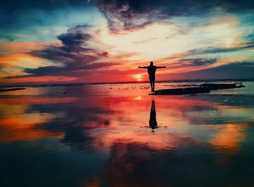Man standing on seashore rocks, calm sea, beautiful red sunset