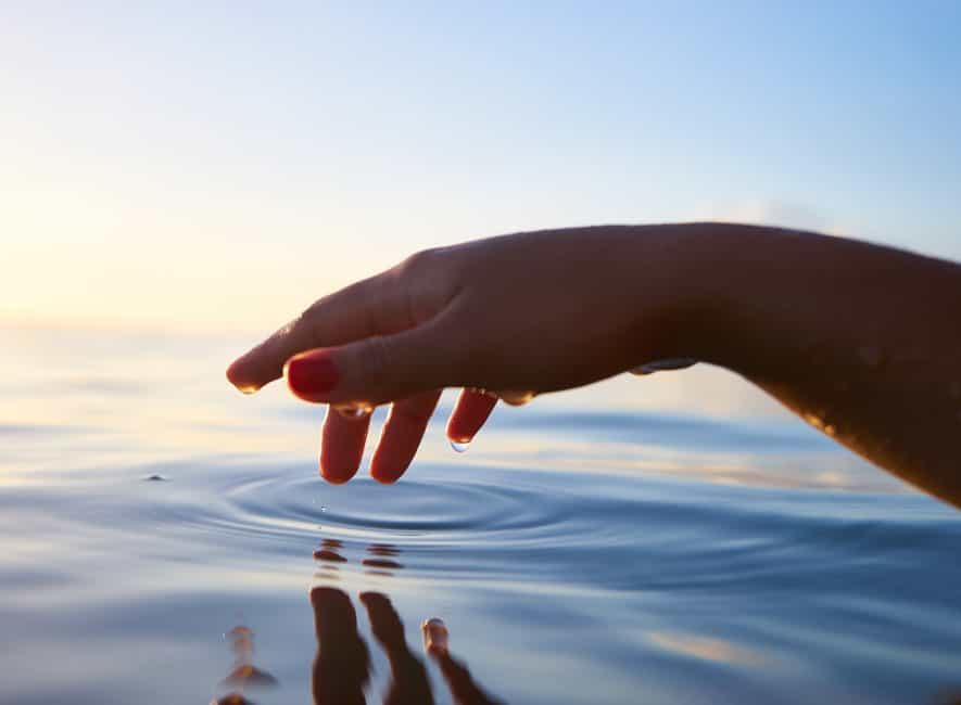 Finger gently touching body of water creating ripples