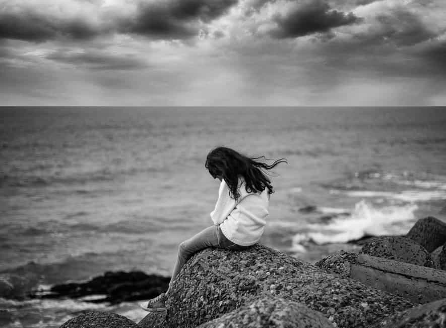 Greyscale photo of young girl sat on rocks head down facing sea