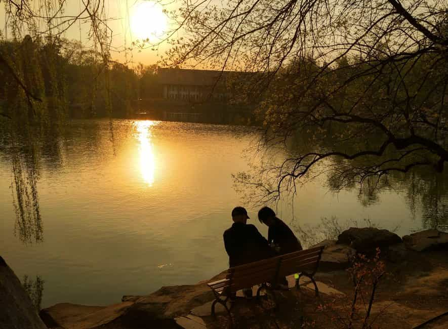 Two people sitting and talking on bench near lake