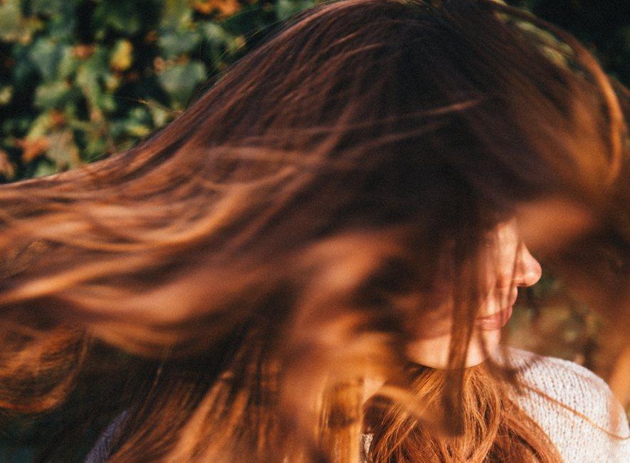 Red-haired woman shaking long hair, face obscured