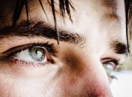 Close-up photo of a man's green eyes locked in thought